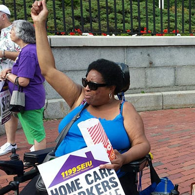 Person in wheelchair holds fist in the air outside the State House.