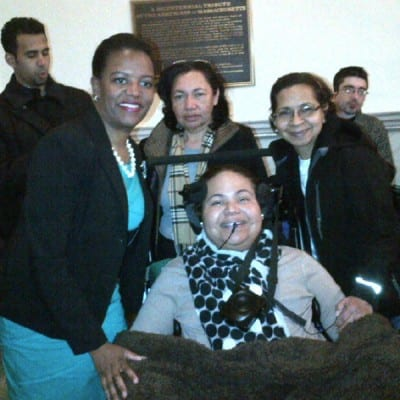 A Massachusetts senator takes a picture with three other people, one in a wheelchair.