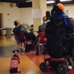 Back view of a person in a wheelchair has a service dog.