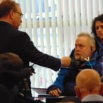 A person in a dark suit jacket, blue shirt and yellow tie speaks to a person in a wheelchair.
