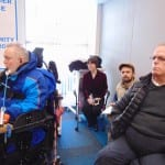 Three people seated in chairs and a person in a wheelchair listen to the guest speaker.