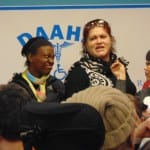 A person in a black and white vest and black sweater speaks into a microphone handed to her.