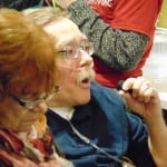 A person with an oxygen tube in their nose speaks into a microphone.