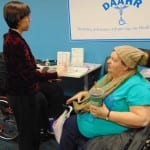 A person in a wheelchair wearing a blue t-shirt and tan wool hat speaks with a person in a black a red shirt.