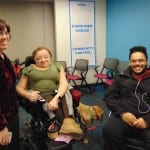 Three people, one in a wheelchair, take a group picture.