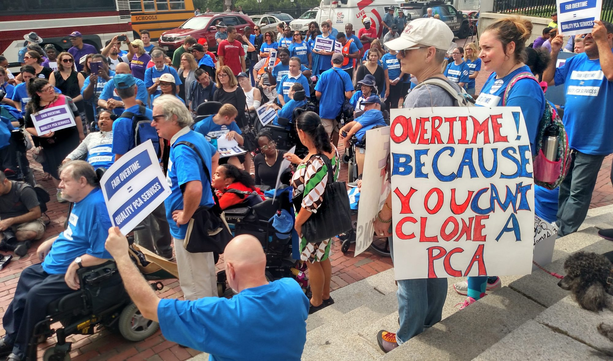A large group of people rally in front of the State House wearing blue t-shirts. Sign reads Overtime! Because You Can't Clone A PCA!