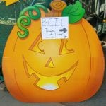 Smiling pumpkin points direction to event.