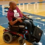 A person in a red polo does laps for the fun run in their wheelchair.