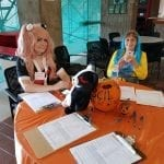 Staff in costume seated at the registration table.
