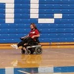Two people do laps in their wheelchairs while another person in gym clothes jogs ahead.