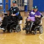 Two people do laps in their wheelchairs.