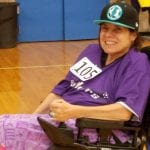 A person in a purple t-shirt and black hat smiles in their wheelchair wearing the number 105.