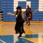 A person wearing a black gown and a gladiator dance while completing laps.
