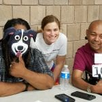 Three people gathered smiling for a picture - one has a dog mask.