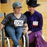 A person in a wheelchair poses with a person dressed in Victorian era clothing.