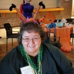 Person smiles for picture wearing witch headband and dollar sign necklaces.