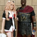 A staff member dressed as a schoolgirl poses with a person dressed as a gladiator.