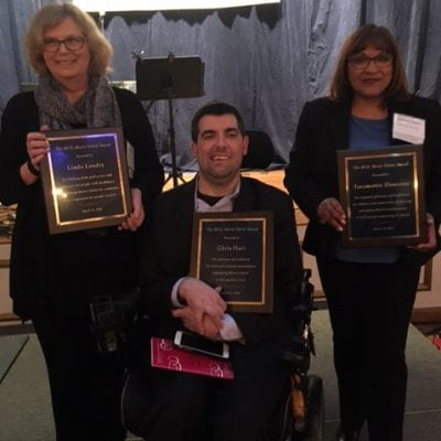 Three people, one in a wheelchair, present their awards at event.