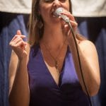A person in a blue dress sings into a microphone.