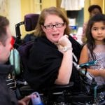 A person in a wheelchair wearing a black shawl speaks with another guest while a child stands next to them.