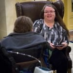 A person wearing a gray dress sits in a highback chair speaking to a person in a wheelchair.