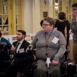 A person in wheelchair listens in on a conversation.