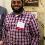 Staff member in checkered shirt smiles at camera for photo outside the grand ballroom.