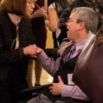 A staff member shakes hands with a person in a wheelchair.