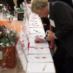 A person wearing a dark suit writes a bid on an item in the silent auction.
