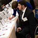 A person wearing a suit in a wheelchair examines some of the silent auction items while another person in a blue dress shirt bids on an item.