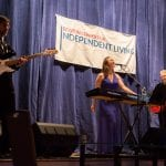 A person in a blue dress stands at an electric keyboard and sings into a microphone while a pair of people in suits play guitars.