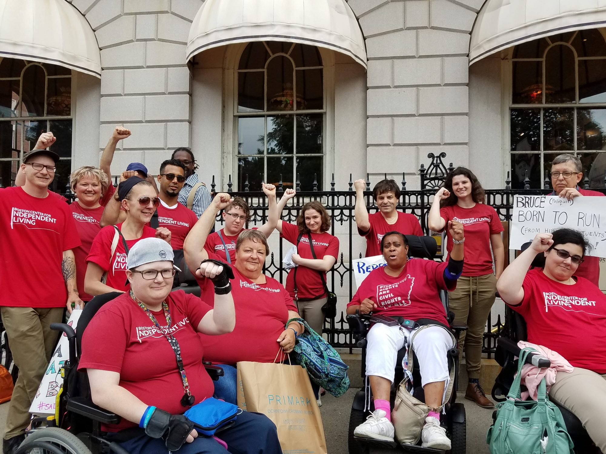 Fifteen people wearing red Boston Center for Independent Living t-shirts smiling and holding their fists in the air.