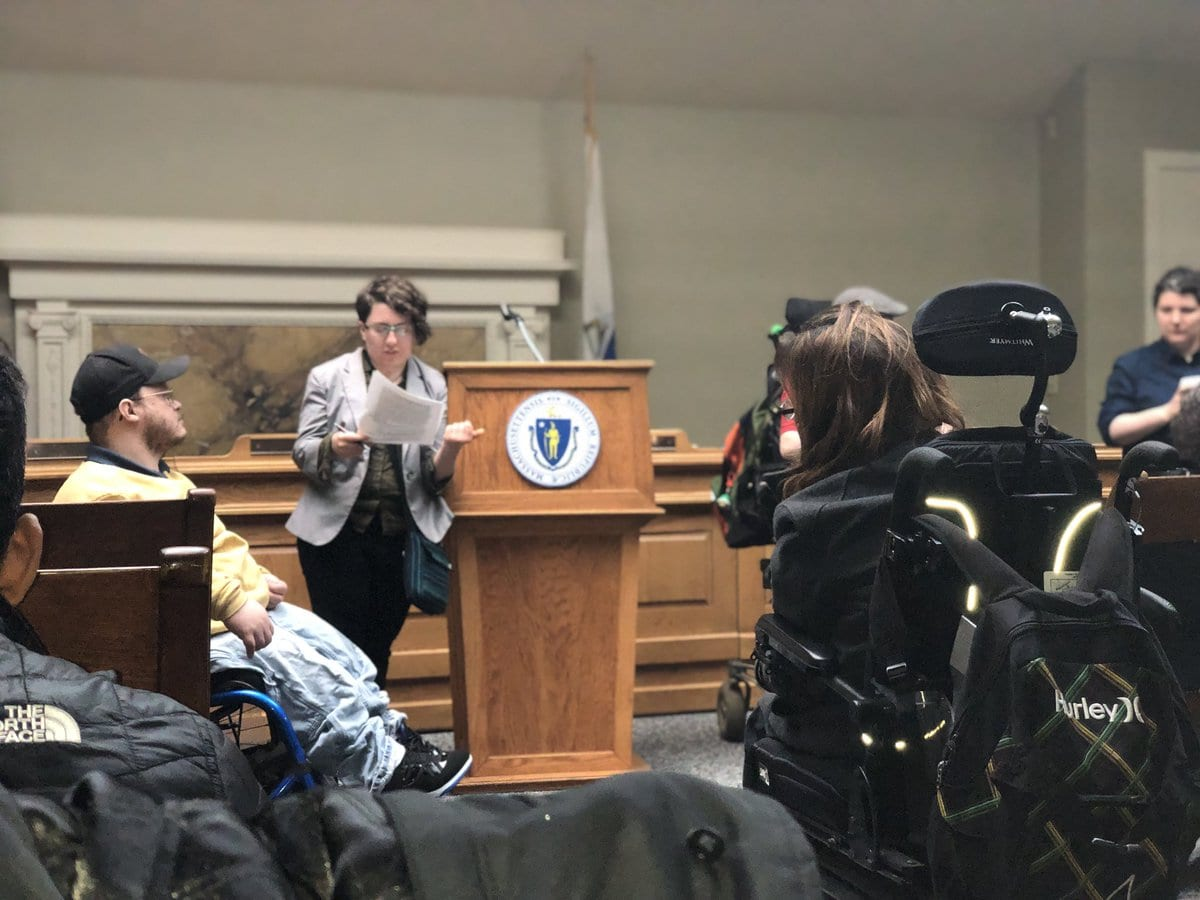 Four people in wheelchairs listen as a person in a gray jacket speaks at a podium.