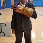 A costumed participant wearing a suit, hat, purple mask and glowing gauntlet poses for a photo.