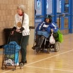 A person wearing a white sweater walks with a pushcart while a person wearing a blue jacket and the number 114 follows behind in a wheelchair.
