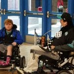 Two people using wheelchairs get ready for a soccer game. One wears the number 115 on the front of their black jacket.