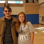 A person wearing sunglasses and a brown jacket takes a picture with a person in a gray t-shirt with the number 113 on it.