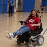 A person in a wheelchair wearing a red BCIL t-shirt with the number 110 on the front participates in the run while a person in a blue t-shirt jogs in the background.