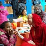 A child wearing a pink jacket looks at the camera while a person in a red cloak applies face paint.
