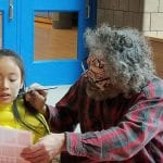 A person wearing a yellow jacket participates in face painting from a person with zombie makeup.