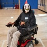A person wearing a grinning mask and black cloak poses for a photo in their wheelchair.