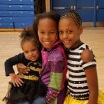 Three costumed children smile for a group photo.