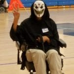 A person wearing a grinning mask and black cloak gives a peace sign as they complete laps in their wheelchair.