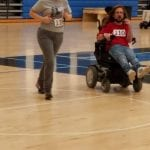 A person wearing a grey t-shirt jogs with a person in a wheelchair wearing a red shirt.