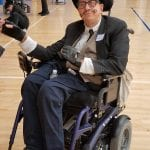 A person in a wheelchair wearing a suit, top hat and fake mustache poses for a photo.