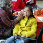 A child wearing a yellow jacket waits patiently while a person with zombie makeup applies a face painting.