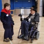 A person in a wheelchair wearing a suit and top hat converses with a person in a long blue robe with red collar.