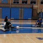 A pair of people in wheelchairs participate in a game of soccer.