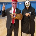 A person in a suit, hat and Thanos mask poses with a cloaked figure wearing a grinning mask.