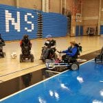 Six people in wheelchairs participate in a game of soccer.